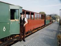 one end of the brakevan, with the guard in smart uniform standing on the platform