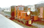 red diesel locomotive with one coach