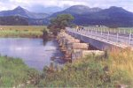 bridge piers across wide river; road bridge beside disused railway; mountain panorama beyond